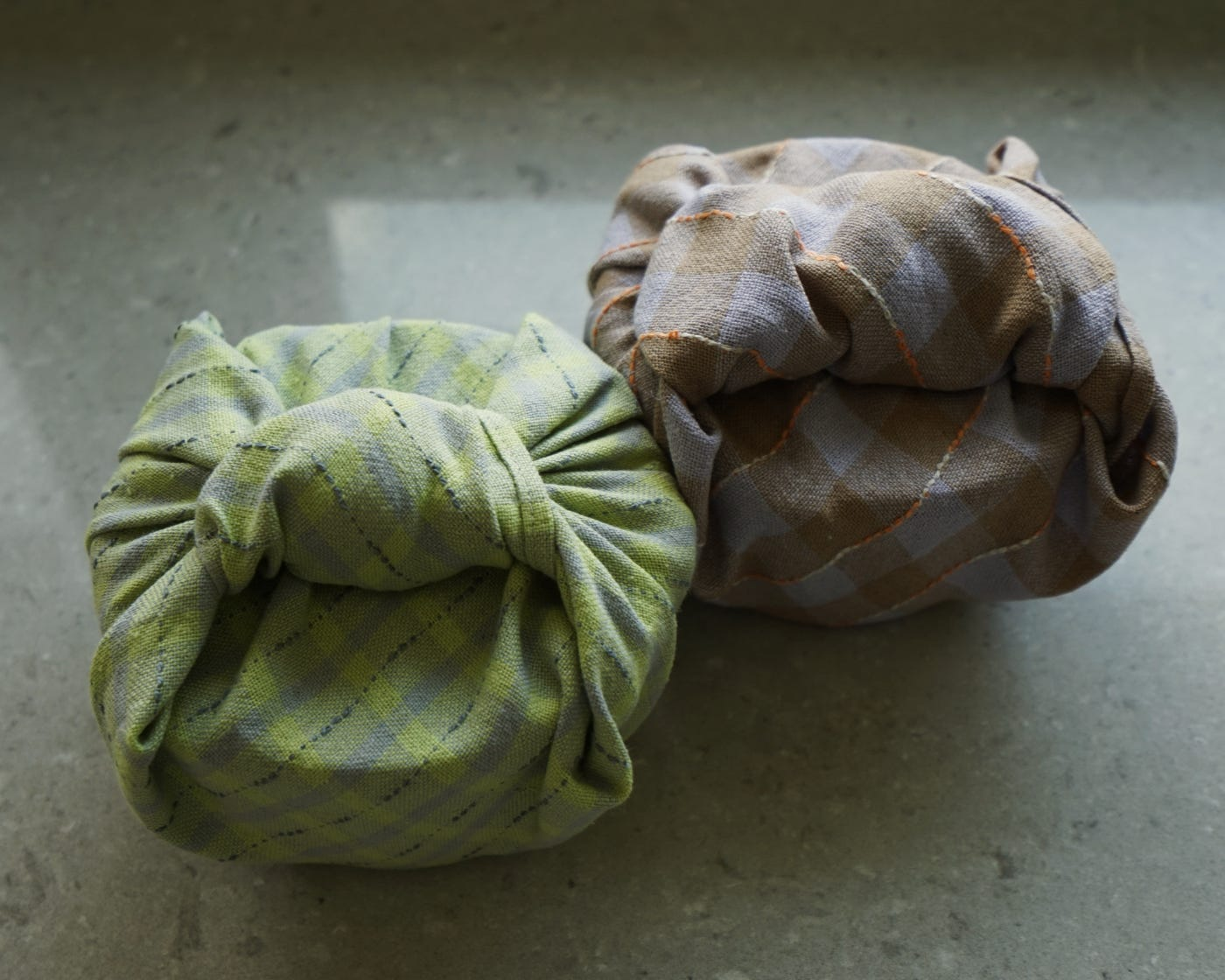 Two containers wrapped in cloth sit next to each other on a countertop.