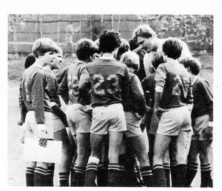 A black and white image of the soccer team in a huddle: boys in long sleeve jerseys and shorts and knee socks. Todd's back is to the camera, and Brian is looking sideways, notebook in hand.