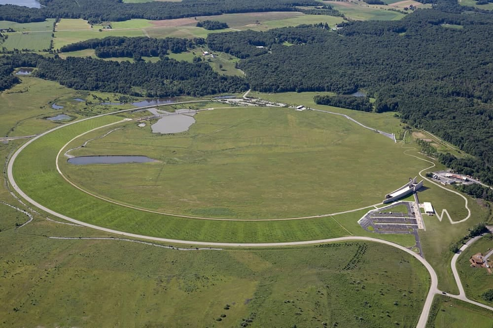 an aerial shot of the Flight 93 memorial site in Shanksville, PA, with a carved round path, open green, and memorial structures for visitors.