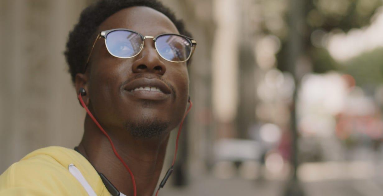 Cena do filme Two distant strangers: close em um homem negro de óculos, cavanhaque ralo, moletom amarelo e fones de ouvido com cordão vermelho, olhando para cima enquanto sorri