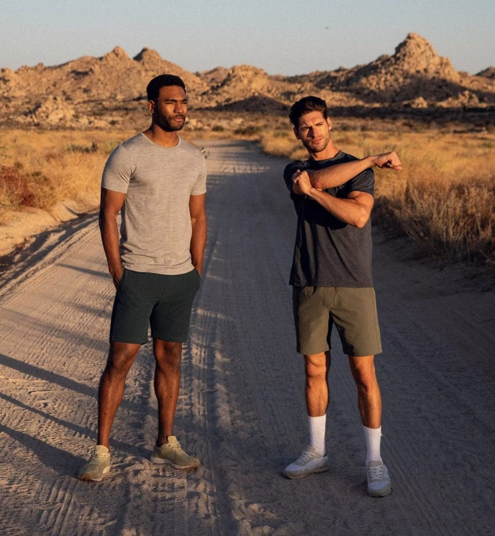 two men wearing olivers all over shorts stretch their muscles for a sunset run