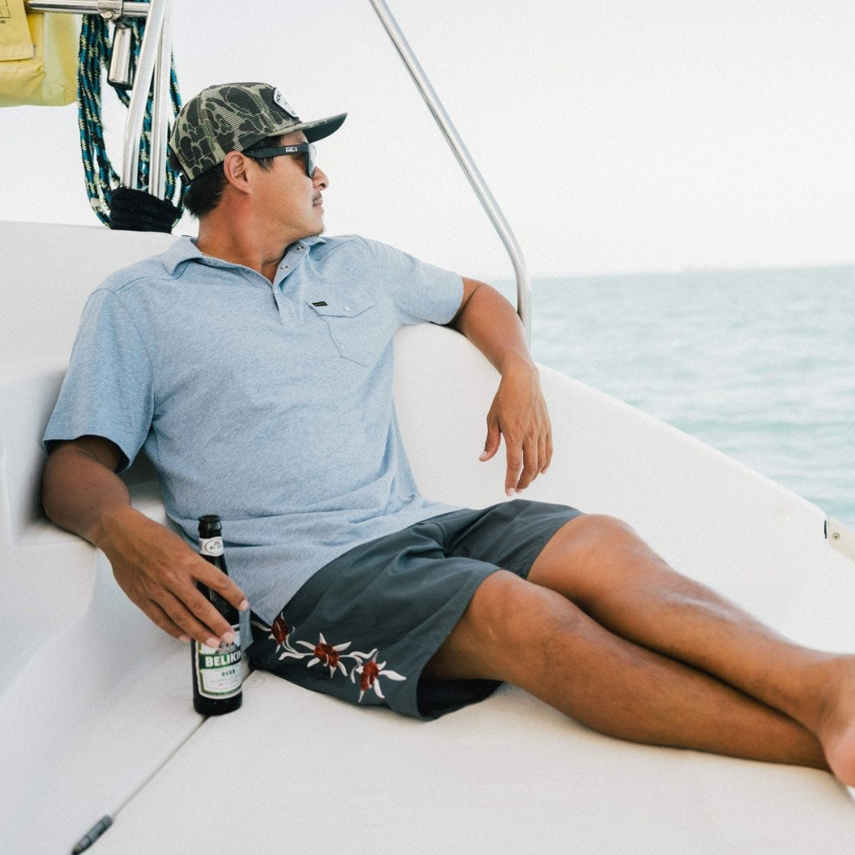 a man on a boat wears the howler brothers ranchero polo