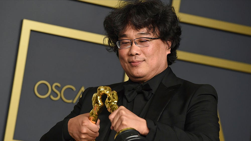 """Bong Joon Ho poses in the press room with the awards for best director for """"Parasite"""" and for best international feature film for """"Parasite"""" from South Korea at the Oscars, at the Dolby Theatre in Los Angeles92nd Academy Awards - Press Room, Los Angeles, USA - 09 Feb 2020"""