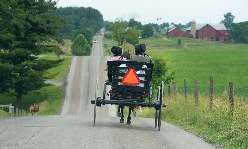 photo of two person riding on black carriage running on grey concrete road