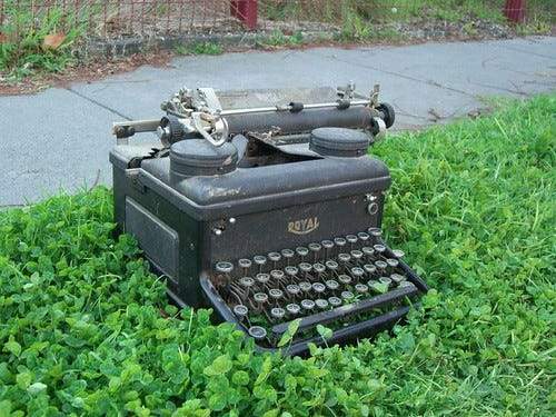 """An old Royal typewriter sits in some grass next to a sidewalk. """"Royal Typewriter"""" by avlxyz is licensed under CC BY-SA 2.0"""