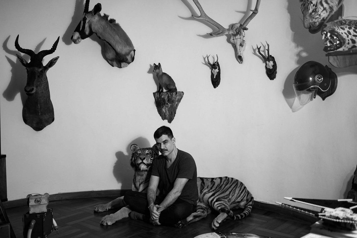 iamgem em preto e branco mostra homem sentado numa sala cercado de animais espalhados como uma onça e uma raposa, ele vesta ecalça e camiseta preta e olha diretamente para a câmera.