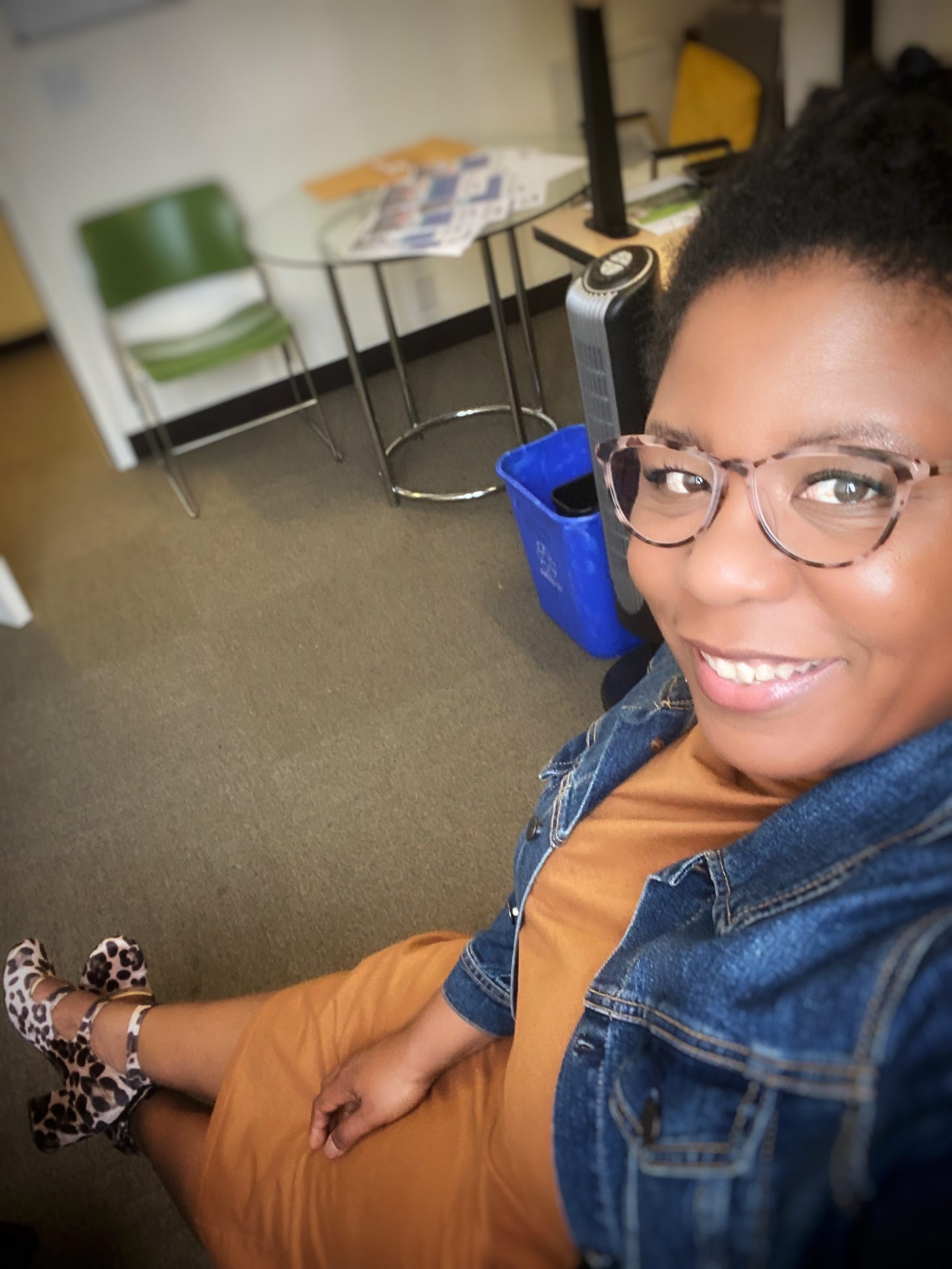 Qianya sits at a desk with her legs in front of her, smiling up towards the camera.  She is wearing a mustard dress with a blue denim jacket.  She has on kick ass cool leopard print block heel shoes and cat eyes glasses.