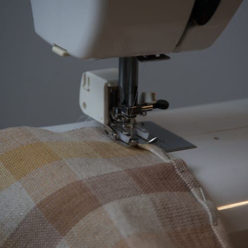 Handwoven fabric feeding into a sewing machine.