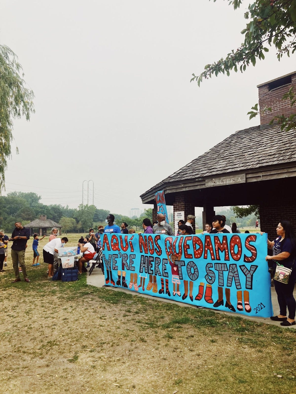 """a group of people stand in front of a shelter at a park holding a bright blue sign with red and grey letters reading """"aquí nos quedamos/we're here to stay"""" above paintings of feet"""