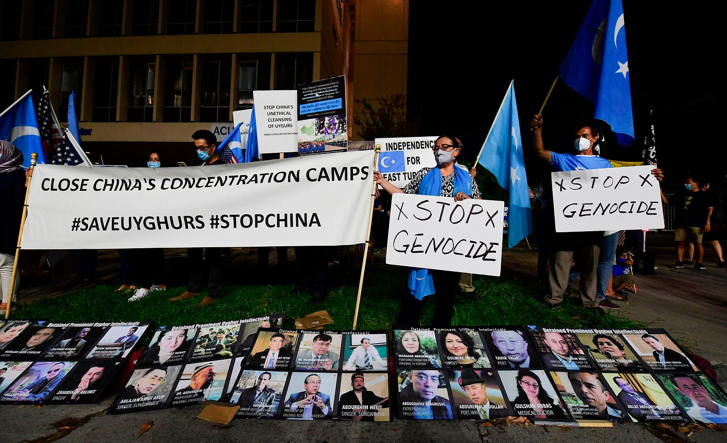"""Protesters stand behind a display of photographs of prominent Uighur intellectuals detained by China as they gather across from the Chinese Consulate in Los Angeles on October 1, 2020 during a global day of action called by """"Resist China"""" (#ResistChina), a global campaign against the regime of the Chinese Communist Party. (Photo by Frederic J. BROWN / AFP) (Photo by FREDERIC J. BROWN/AFP via Getty Images)"""