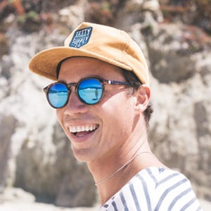 a man wearing the sunski dipsea sunglasses smiles at the beach