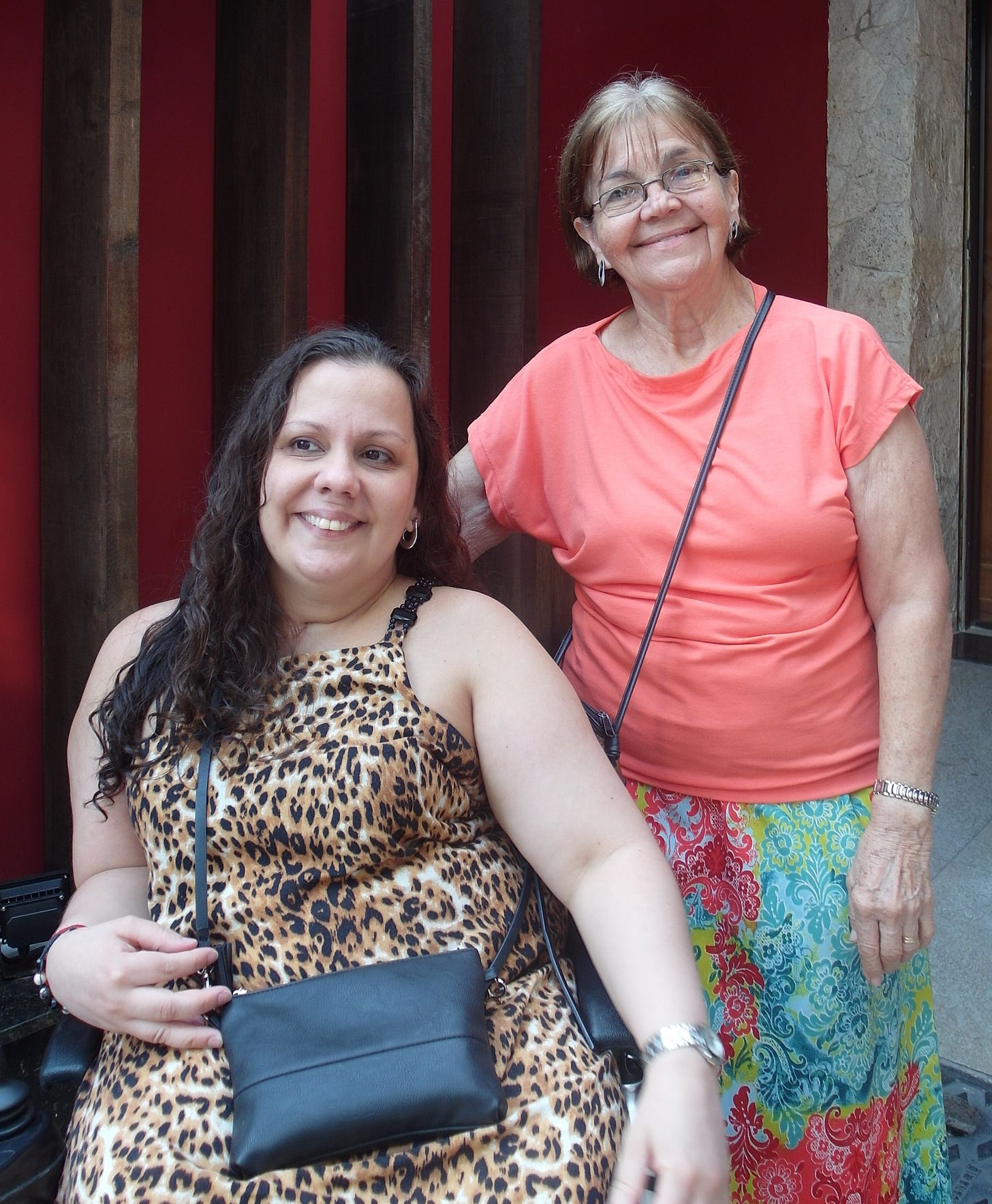 Sheila smiles with a glance off camera, dark hair curling down, sitting in a wheelchair with a leopard-print dress. Raylda to her right is an older woman smiling towards the camera and rose coloured top and colourful print dress.