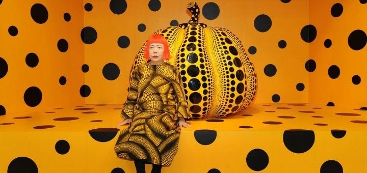 Yayoi Jusama in front of a large pumpkin sculpture