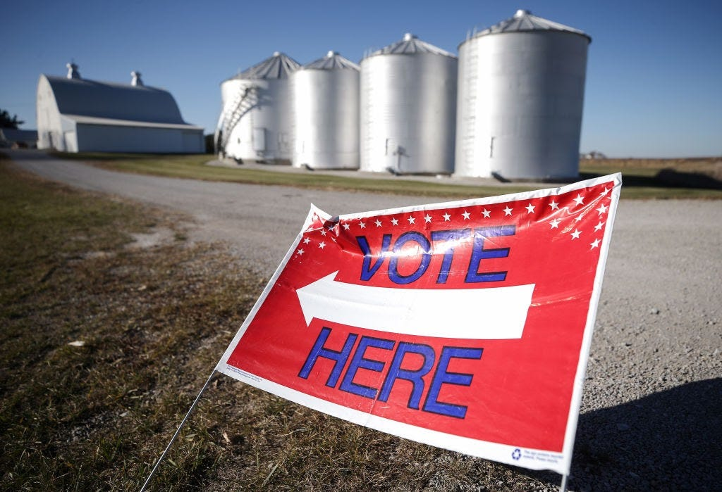 """A """"Vote Here"""" sign points voters toward a polling place in Ray Lounsberry's shed on November 3, 2020, in Nevada, Iowa. (Photo by Mario Tama/Getty Images)"""
