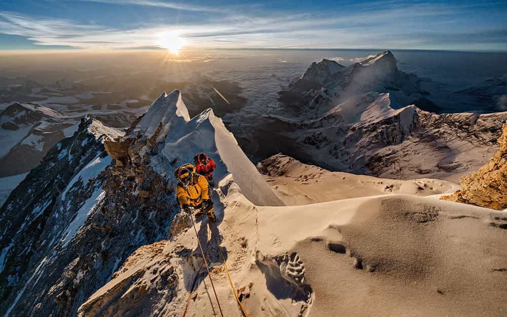 men climb mount everest on a sunny day