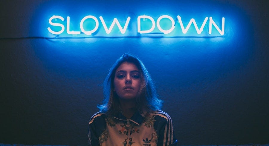 """Young woman under neon sign """"Slow Down"""""""
