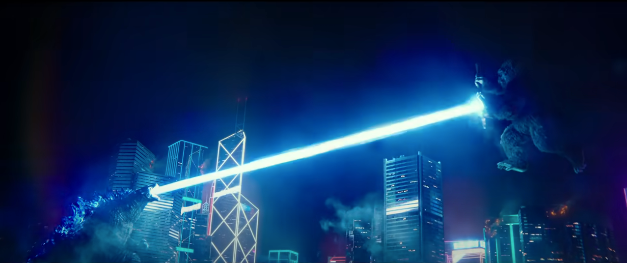 From the film 'Godzilla vs. Kong': Towering over Hong Kong buildings at night, Godzilla fires atomic breath at a charging King King, who is blocking with a special axe.