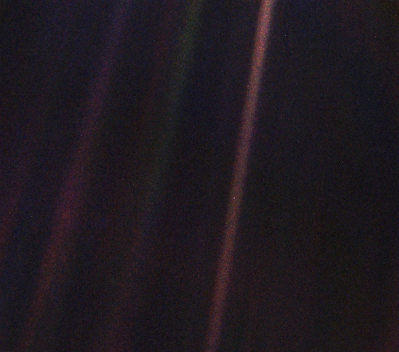 Earth as a small blue dot in a fuzzy beam of light.