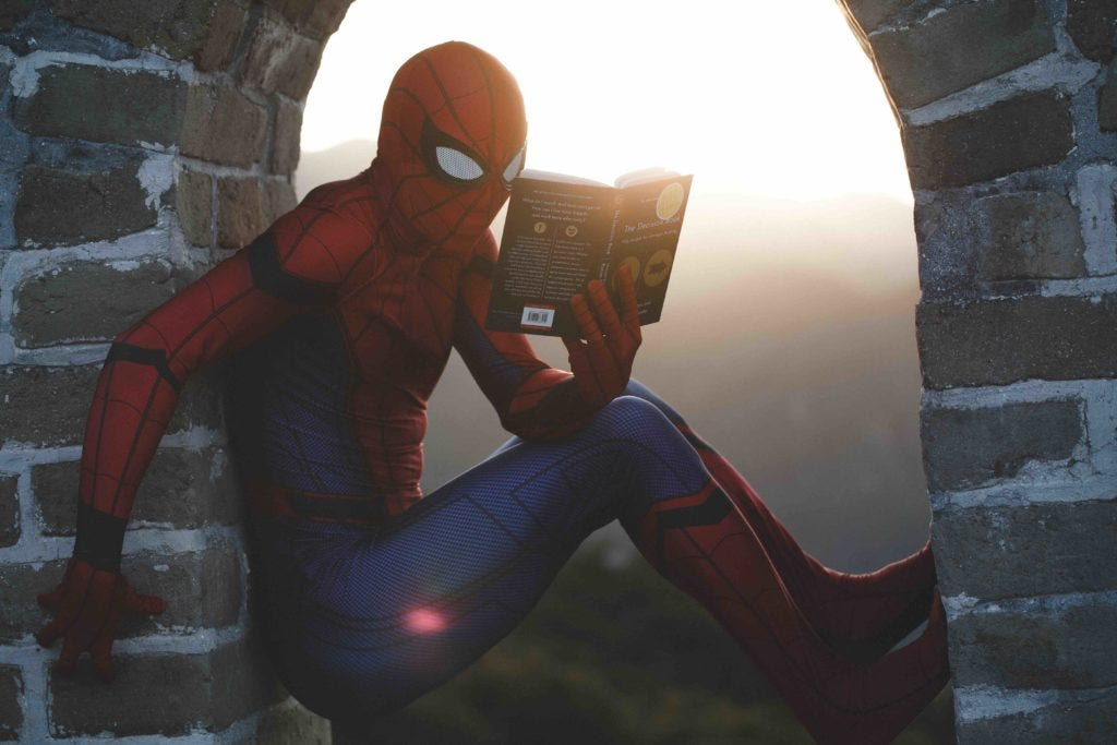 Spiderman increasing his knowledge with a book