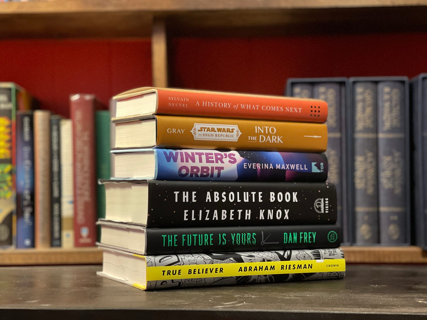 A colorful stack of books sits on a brown table, with a bookshelf in the background.
