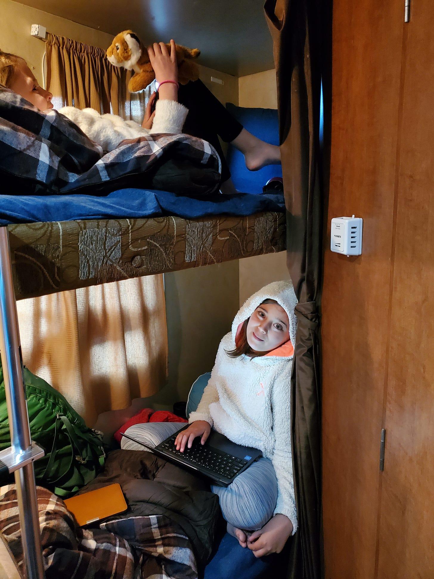 Interior shot of the travel trailer. One girl in the upper bunk and one girl in the lower bunk bed.