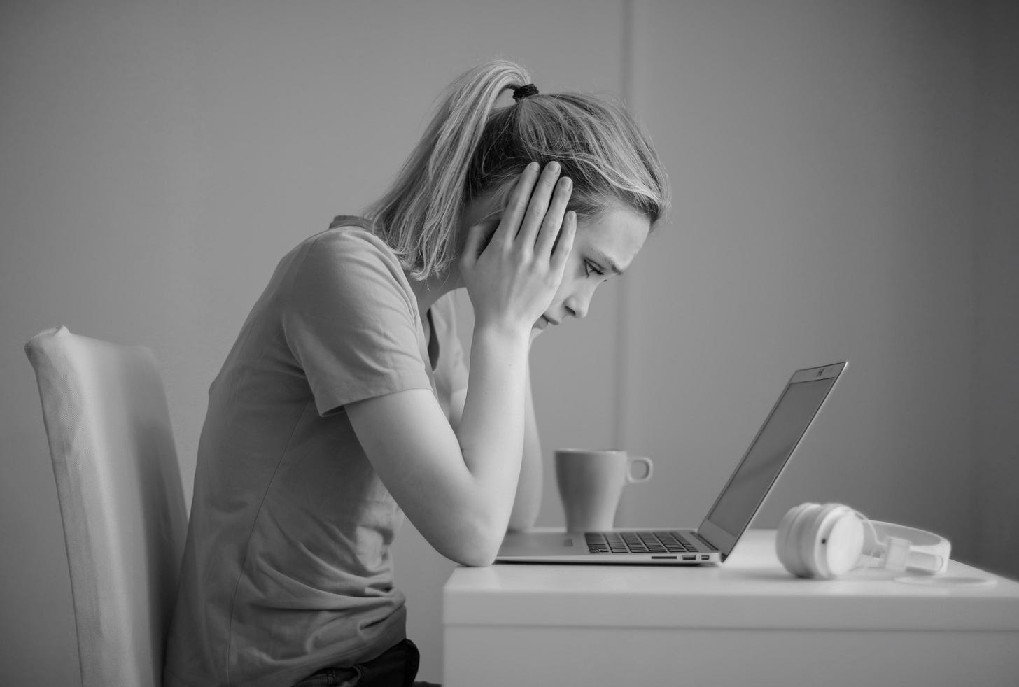 A slender young woman with her hands to her face, looks worried as she stares into her laptop computer screen