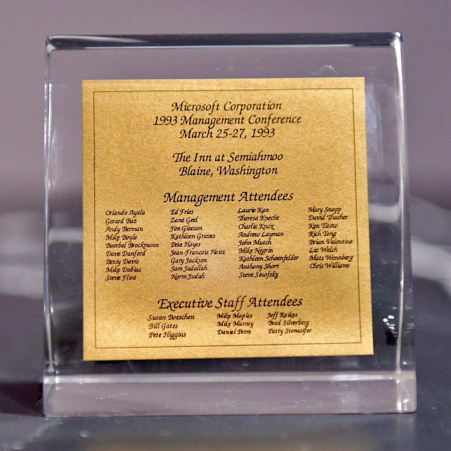 "Lucite block to place on desk. Title is ""Microsoft Corporation 1993 Management conference"" with list of attendees and executive staff."