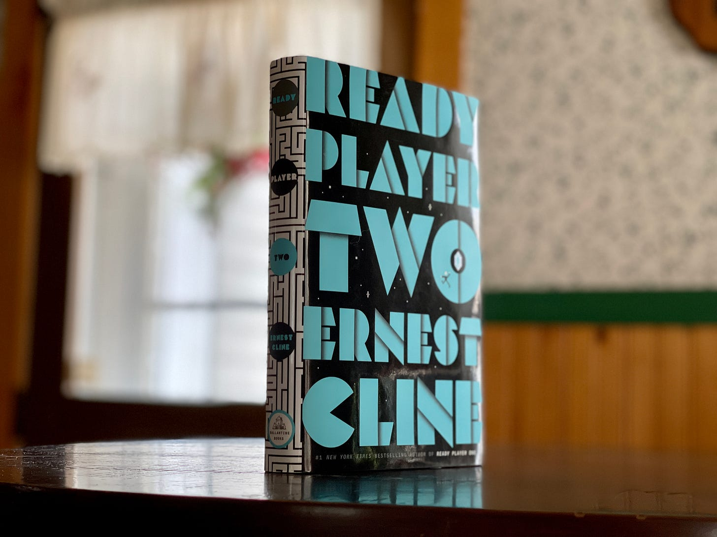 A single copy of Ready Player Two, title and author listed in light blue on a black background, stands on a kitchen table.