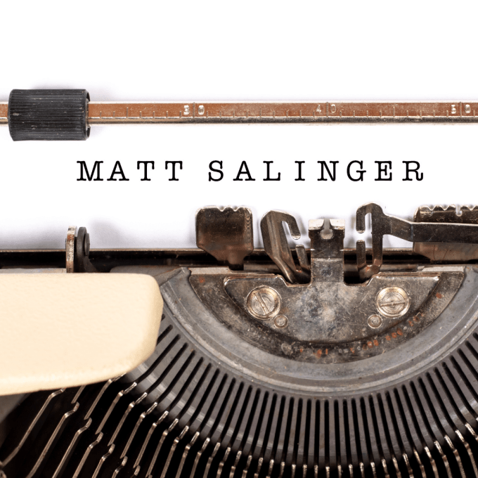 A typewriter with the name, Matt Salinger, typed onto white paper.