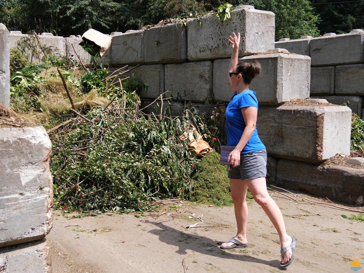 Brunette woman dropping off green waste at the local green waste facility.