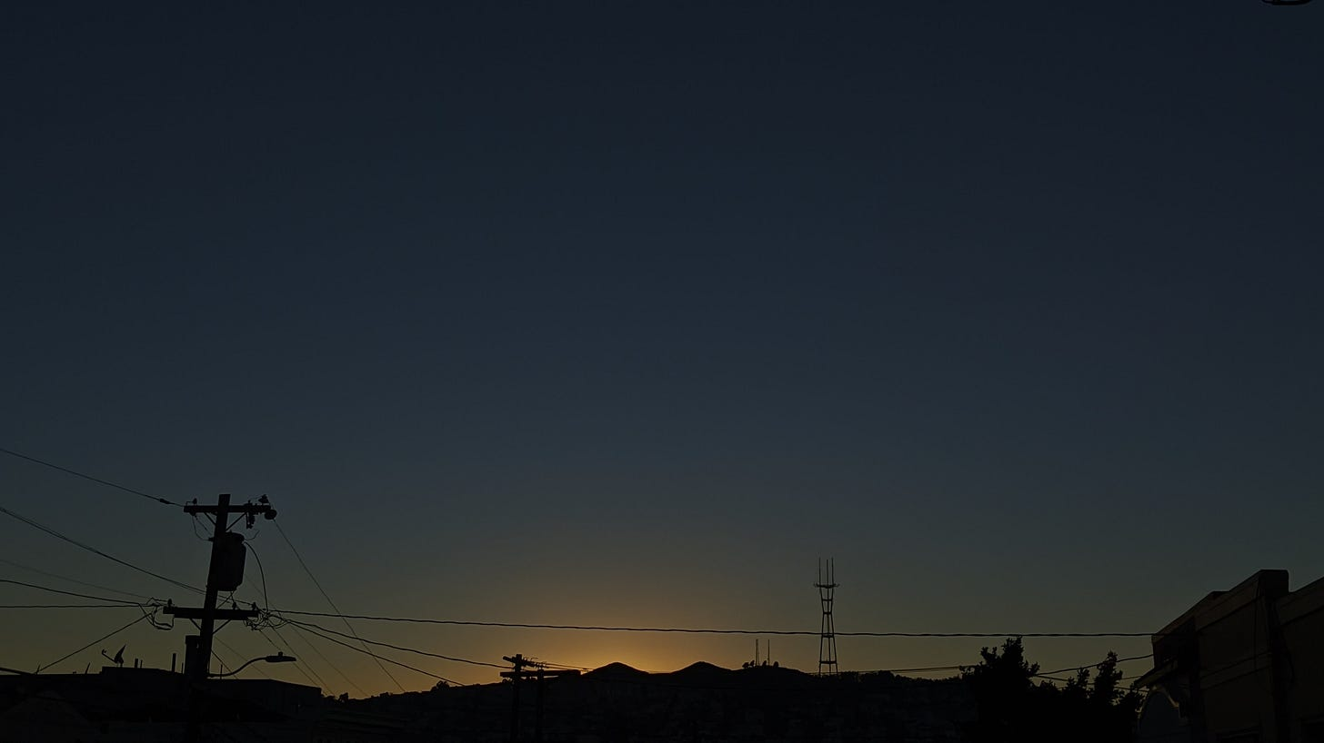A photo looking west in San Francisco during sunset. In the lower third of the photo is the silhouette of Twin Peaks and Sutro Tower. Telephone and power lines criss-cross. The sun has just set behind the two peaks, which is a pale orange. The sky fades from a light turquoise to a dark denim.