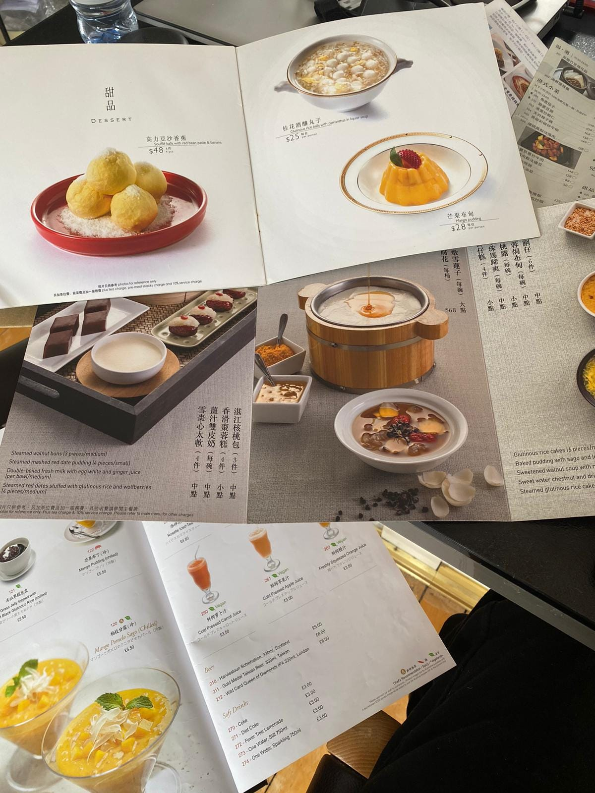 An overhead shot of several Hong Kong restaurant menus open to their dessert pages featuring photos and text