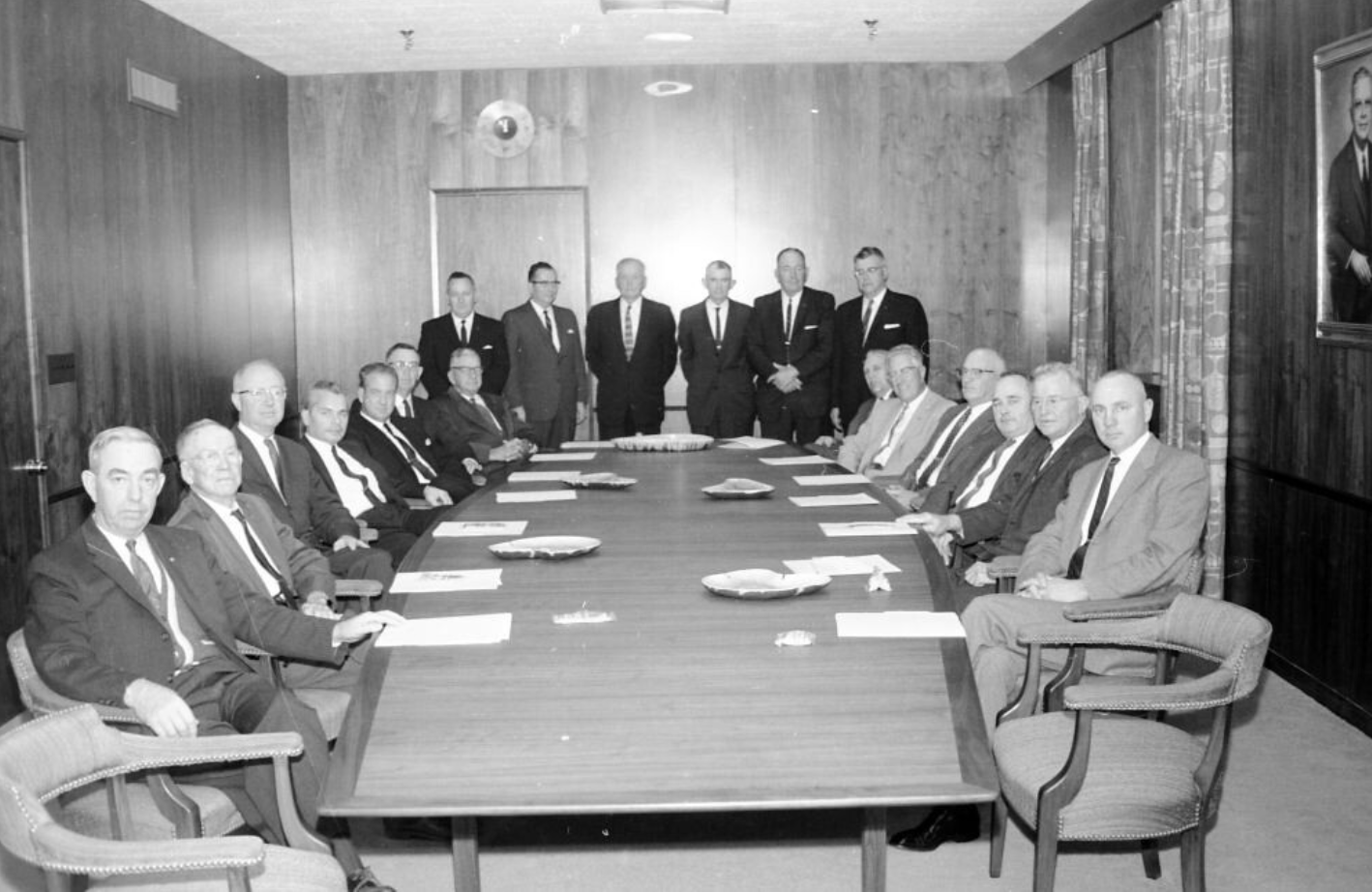 Another picture of men in suits, this one they're all fanned out around a very large table in a wood paneled room