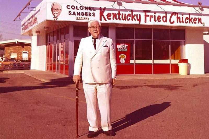 Colonel Sanders standing in front of the KFC restaurant