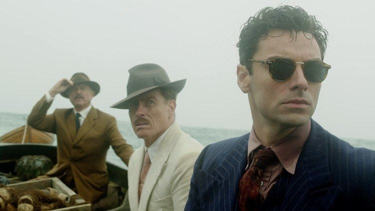 Three men in the AND THEN THERE WERE NONE miniseries on a boat look off-camera with an empty gray horizon stretching behind them