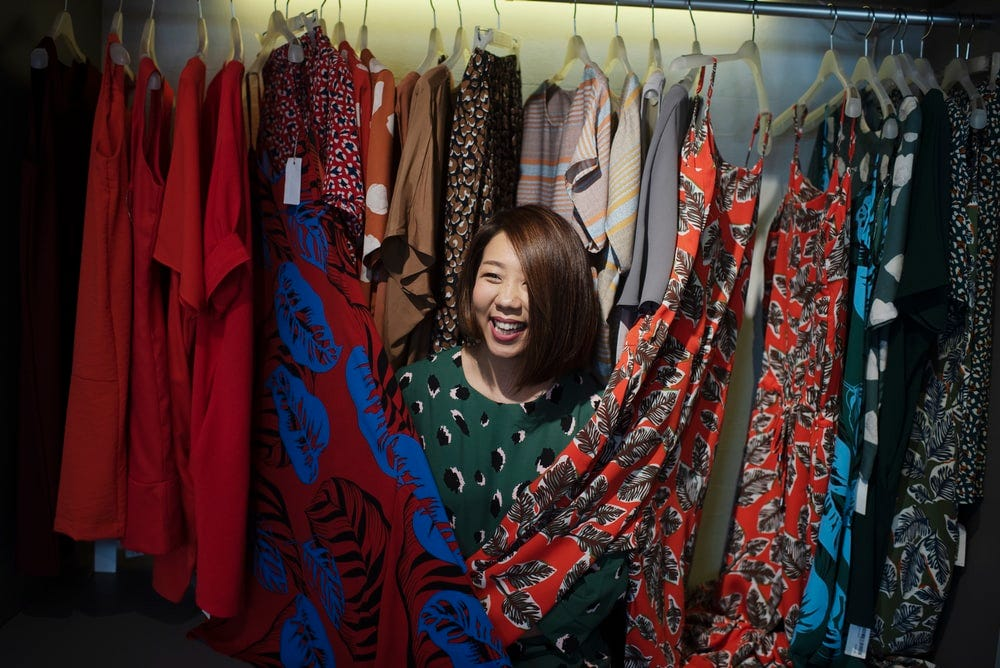 woman hiding behind clothes hanged in wardrobe