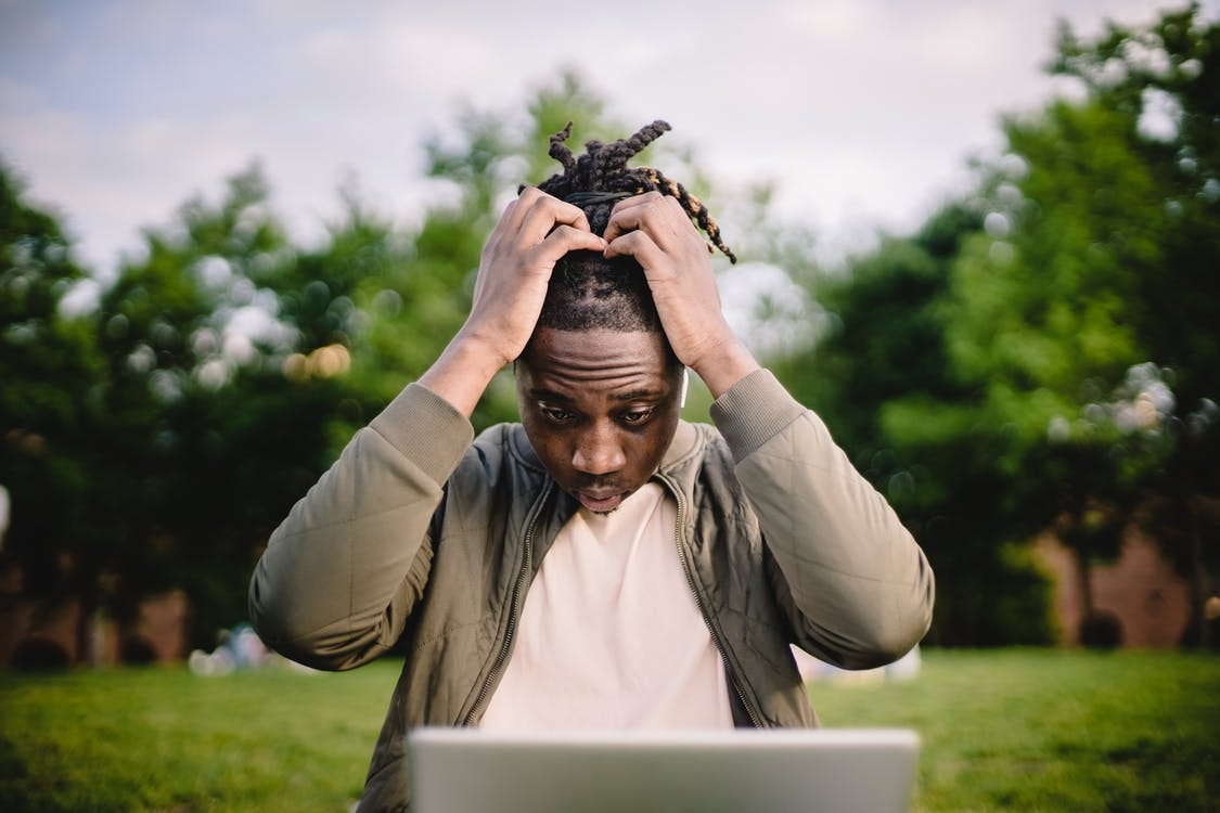 Upset young African American male freelancer clutching head with hands after failure in project while working remotely in park