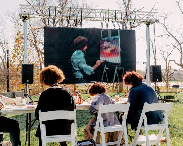 """In Muncie, Ind., Bob Ross fans try their hands at recreating """"Sunset Aglow,"""" from a 1993 episode of """"The Joy of Painting,"""" screened on the lawn near his former studio during the opening of the """"Bob Ross Experience"""" on Saturday."""