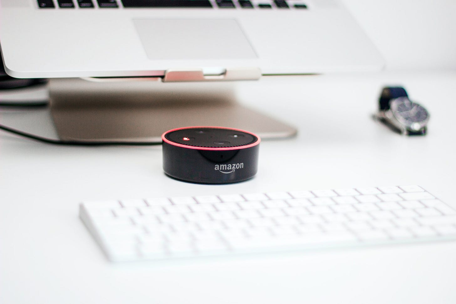 An Amazon Echo Dot showing a red ring in front of a laptop. Piotr Cichosz / Unsplash