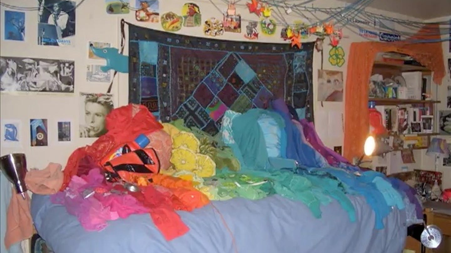 Clothes laid out in rainbow order on a bed, from 2006.