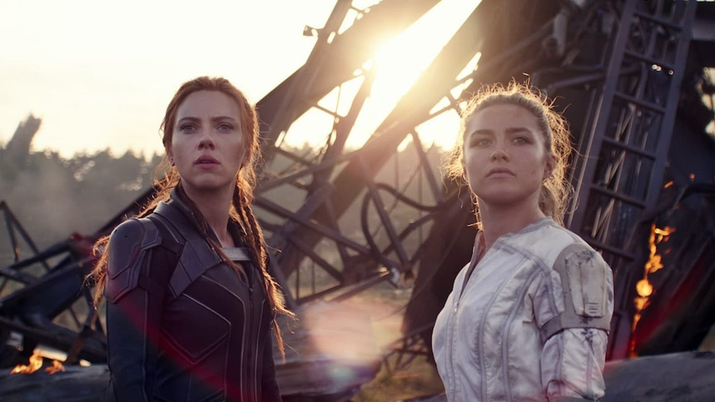 Black Widow and her sister stand and look at the camera with the wreckage of a plane behind them.