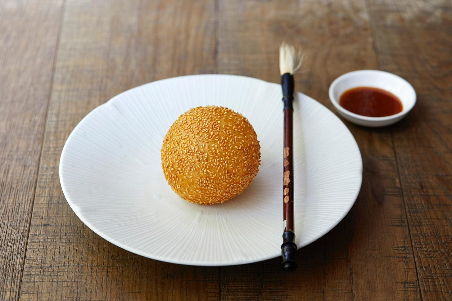A puff ball pastry covered in sesame seeds on a small white plate. On the side of the plate is a paint brush and next to the plate is a small bowl of red coloured sauce. Plate, bowl and brush are on a wooden table