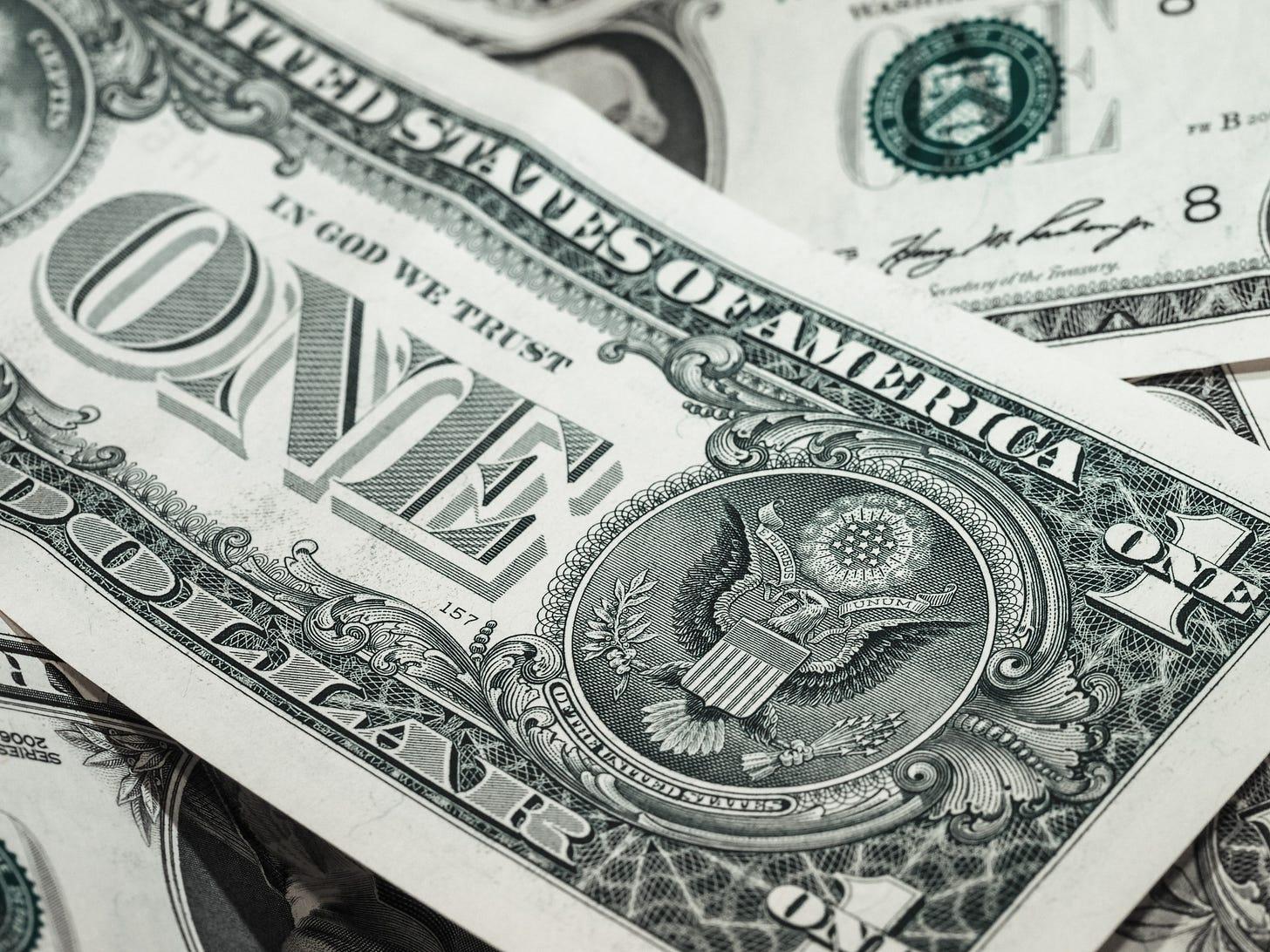 A loose pile of dollar bills, viewed up close