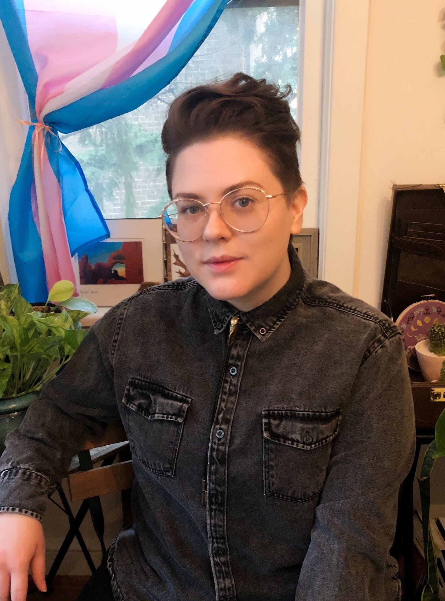 Britt, a white non-binary person with short hair and glasses, sits in front of a trans flag, and near some plants. They wear a long sleeve denim shirt, and metal cicada bolo tie.