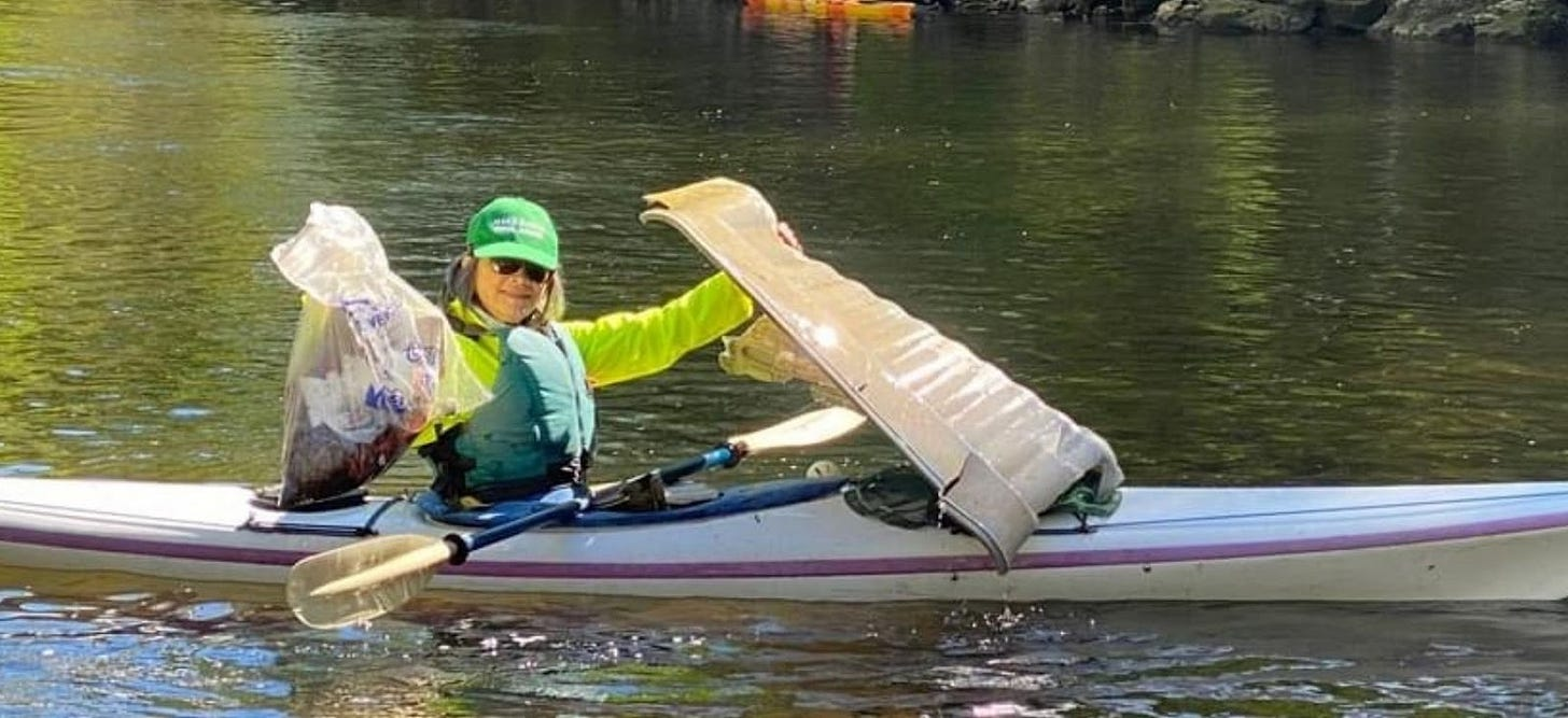 Amy Hall in a kayak, on a river, holding up bags of trash