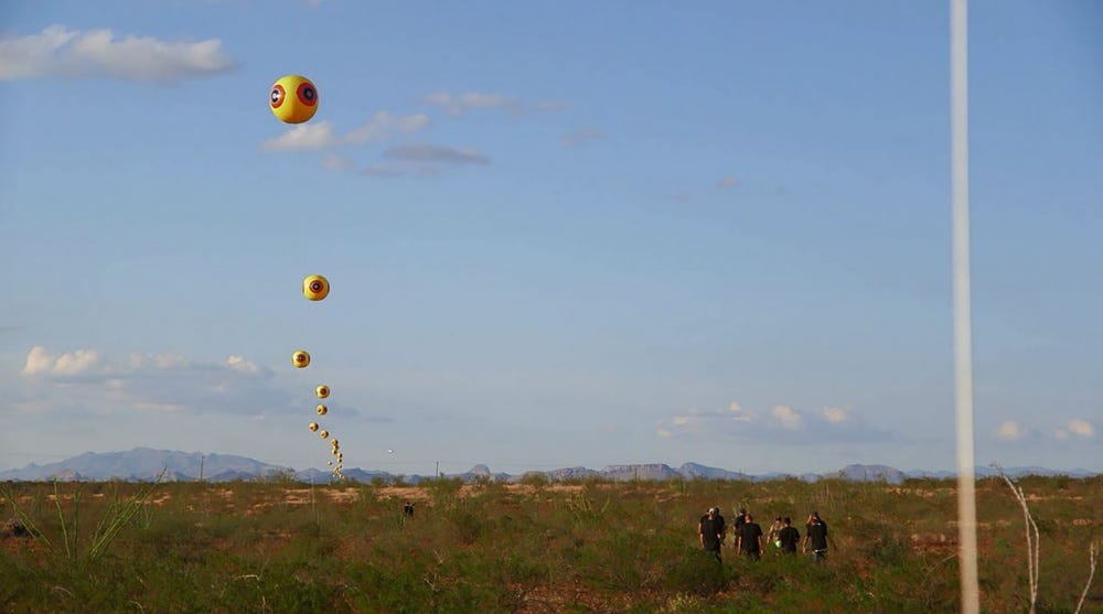 "An image of the desert landscape with mountains just on the horizon and clear skies with a few puffy clouds is cut through on the left third of the image by a series of large yellow balloons. Each balloon has 4 eyes equally spaced around it, each with the colors red yellow and blue making them up. It is imaged after the Indigenous eye iconography, or as its been westernized, the ""scare eye""."