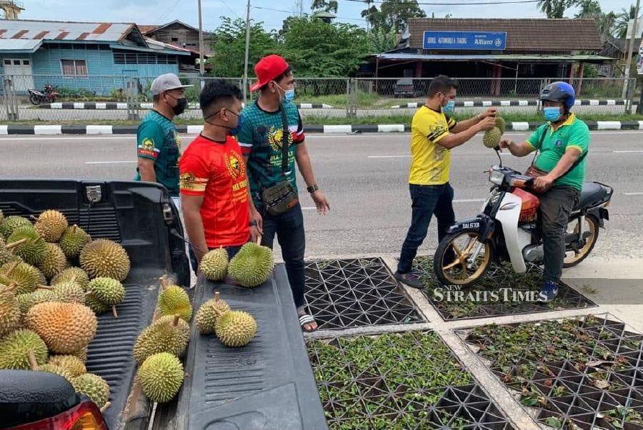 MZ Gold KB distributes free durians to motorists passing through Jalan Pasir Pekan in Tumpat today. - NSTP/SHARIFAH MAHSINAH ABDULLAH