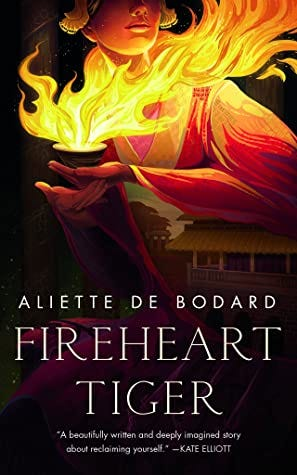 The cover of FIREHEART TIGER features a young femme in a drapey robe cupping a palmful of fire.