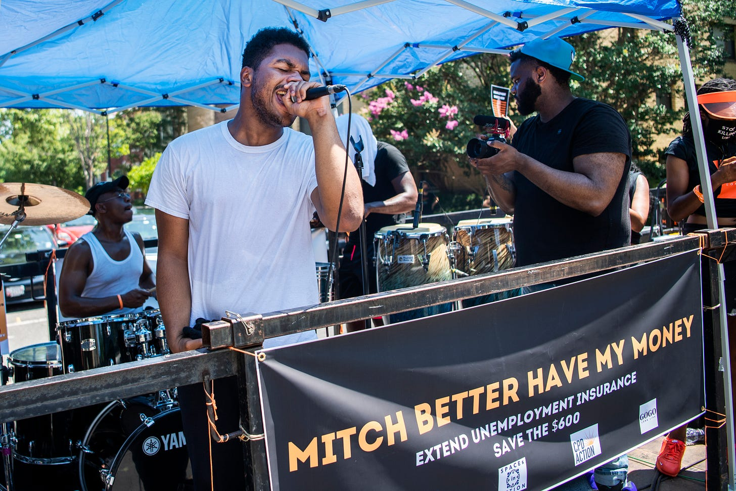 """man singing at a protest with a sign reading """"MITCH BETTER HAVE MY MONEY; extend unemployment insurance; save the $600"""""""