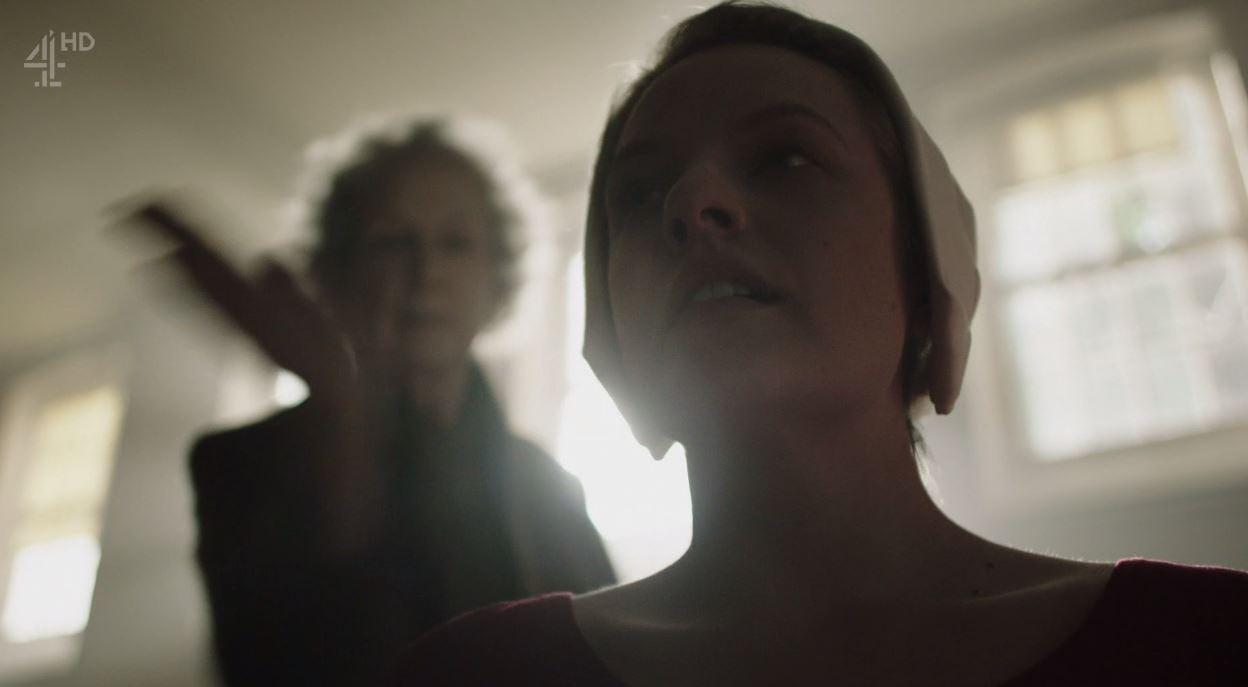 cena da série The Handmaid's Tale. A personagem de Elisabeth Moss na frente, sem perceber a mulher atrás dela, que é Margareth Atwood, com a mão erguida, paralisada no meio do movimento de um tapa que vai acertá-la em cheio